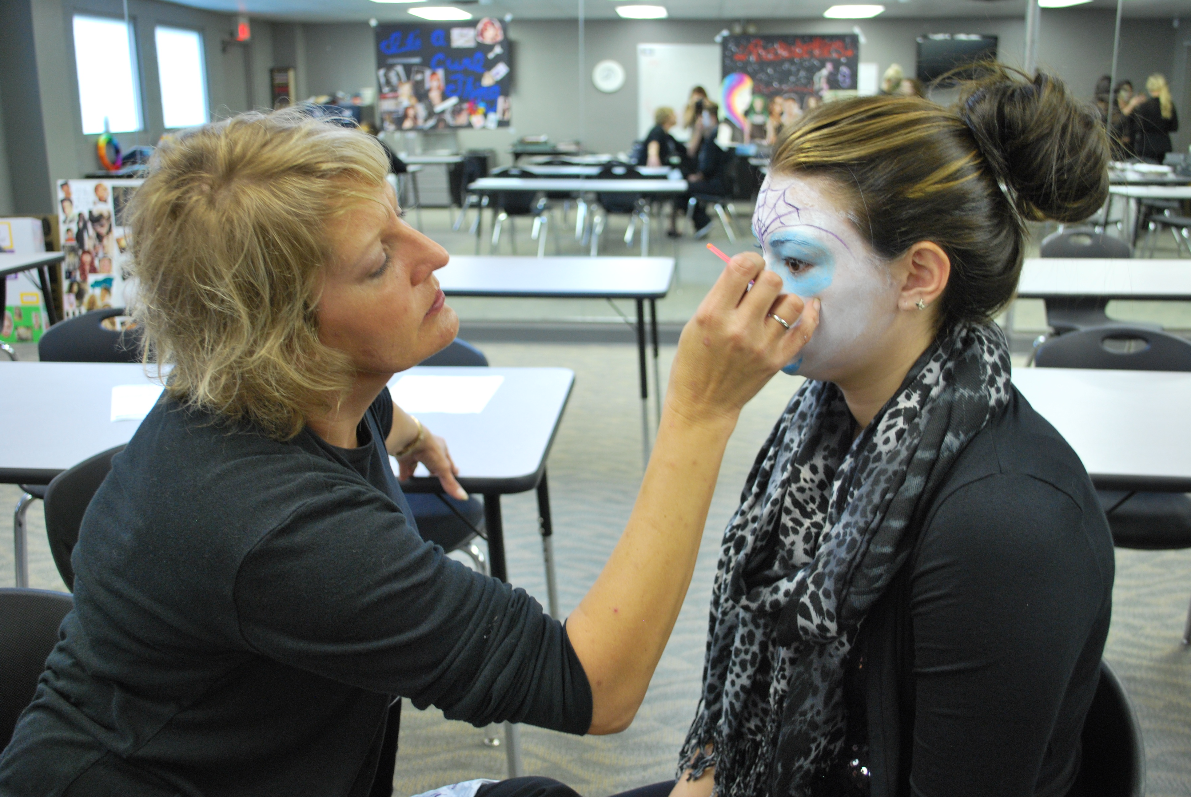 Instructor Kerry Beatty helping with student Katela Norris' Halloween Makeup